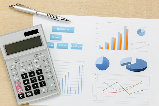 Widok z góry podsumowanie działalności roku i długopis, kalkulator wykresu na biurko drewna biurko.