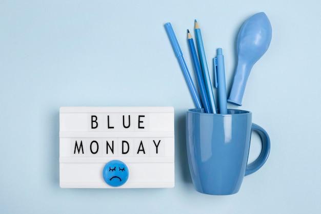 Widok z góry podświetlanego pudełka z kubkiem i balonem na niebieski poniedziałek