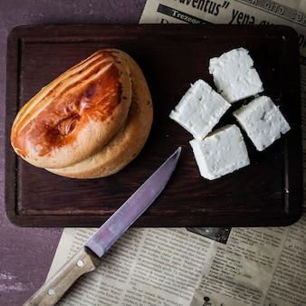 Widok z góry pogaca z serem i nożem i stara gazeta w desce do krojenia
