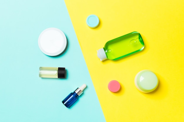 Widok z góry pojemników kosmetycznych, sprayów, słoików i butelek na żółtej i niebieskiej powierzchni