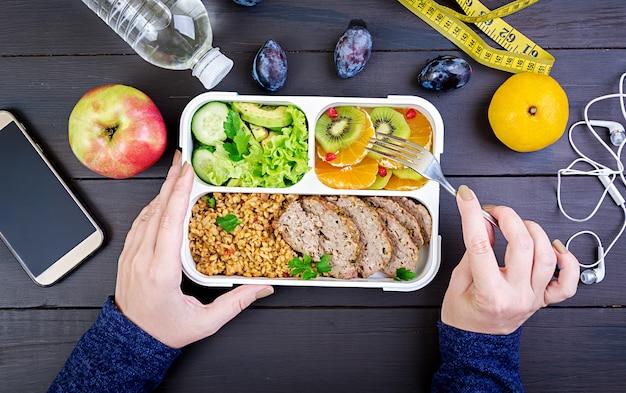 Widok z góry pokazuje ręce jedzące zdrowy lunch z bulgur, mięsem i świeżymi warzywami i owocami