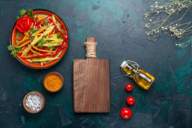 Widok z góry pokrojona papryka zdrowa sałatka z przyprawami i oliwą z oliwek na niebieskim biurku