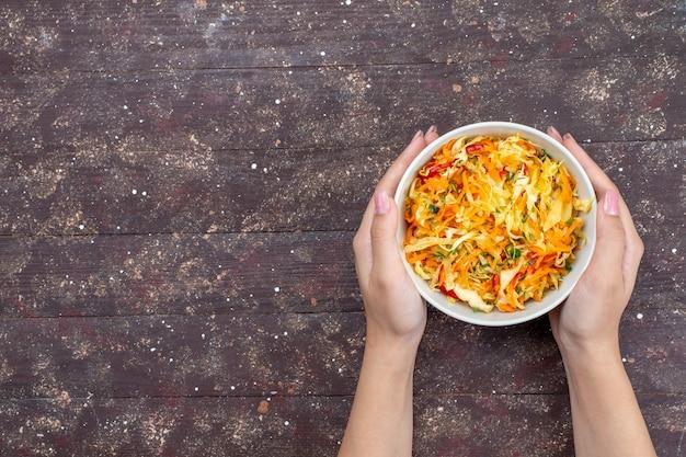 Widok z góry pokrojona sałatka jarzynowa świeże i solone wewnątrz płyty trzymanej przez kobietę na brązowym biurku warzywo danie posiłek posiłek świeże zdjęcie