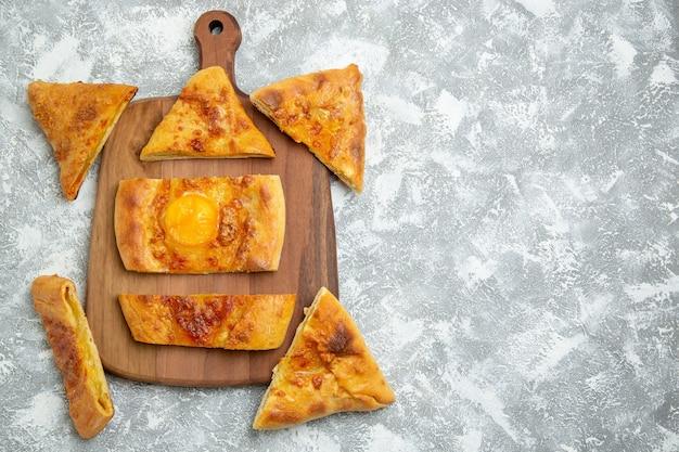 Widok z góry pokrojone jajko upiec pyszne ciasto z przyprawami na białym tle ciasto piec ciasto posiłek pizza jedzenie