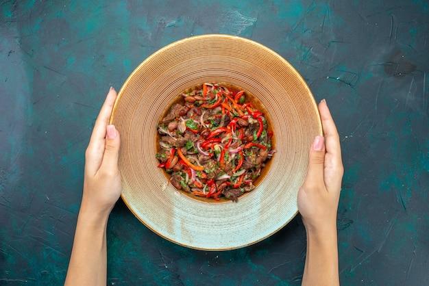 Widok z góry pokrojone mięso z warzywami wewnątrz okrągłego talerza na ciemnoniebieskim stole sałatka z mączki warzywnej