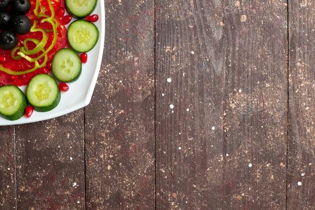 Widok z góry pokrojone ogórki z oliwkami wewnątrz talerza na brązowym rustykalnym biurku dieta sałatkowa witamina witamina