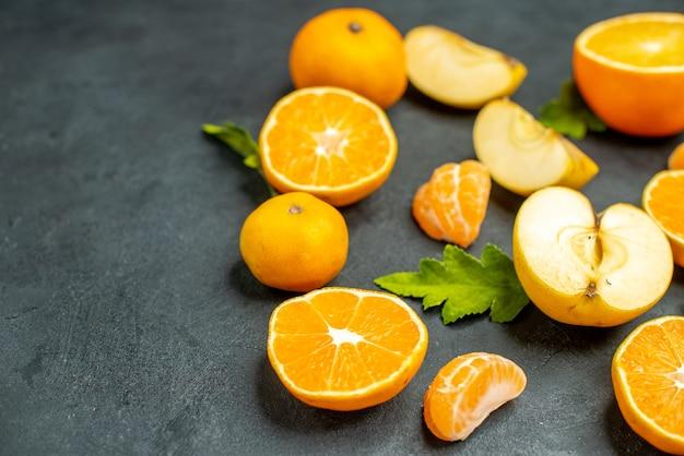 Widok z góry pokrojone pomarańcze i jabłka na ciemnej powierzchni