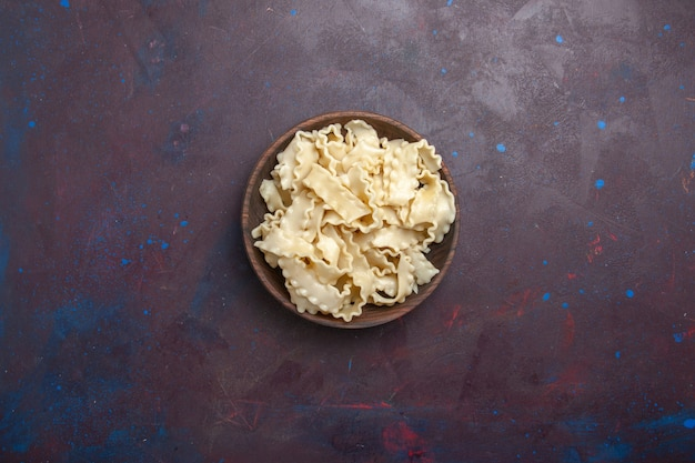 Widok z góry pokrojone surowe ciasto wewnątrz brązowego talerza na ciemnym tle mąka ciasto jedzenie makaronu obiad