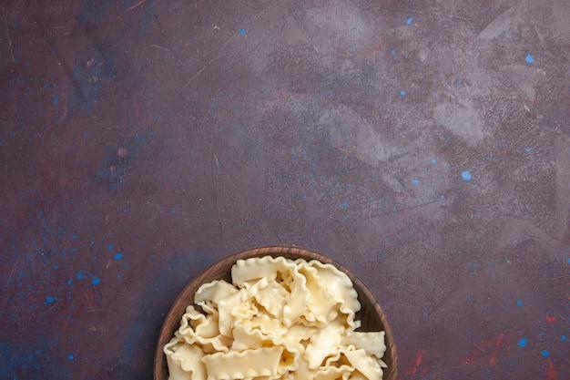 Widok z góry pokrojone surowe ciasto wewnątrz brązowej płyty na ciemnym tle mąka ciasto makaronu obiadowego