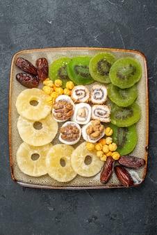 Widok z góry pokrojone suszone owoce krążki ananasa i kiwi na szarym tle suszone owoce rodzynki słodko kwaśne witamina zdrowie