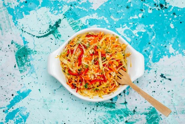 Widok z góry pokrojone świeże sałatki sałatka jarzynowa wewnątrz płyty z łyżką na jasnoniebieskim tle jedzenie posiłek przekąska sałatka jarzynowa