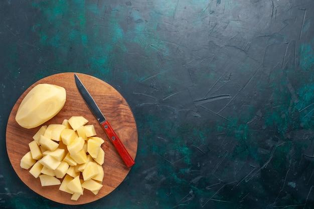 Widok z góry pokrojone świeże ziemniaki warzywa z nożem na ciemnoniebieskim tle