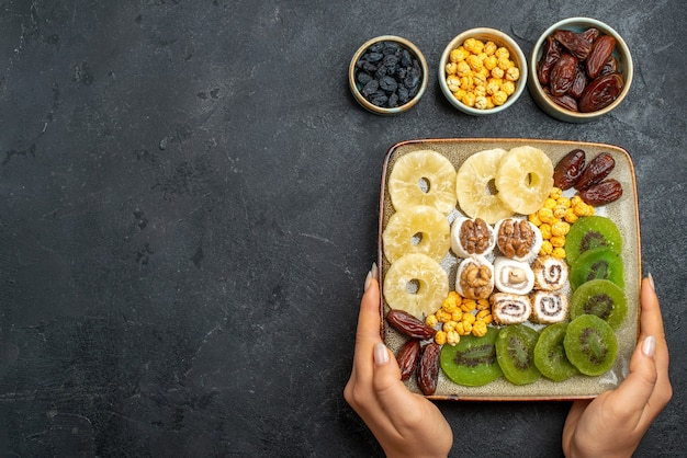 Widok z góry pokrojone w plasterki suszone owoce krążki ananasa i kiwi na szarym biurku suszone owoce rodzynki słodka witamina kwaśne zdrowie