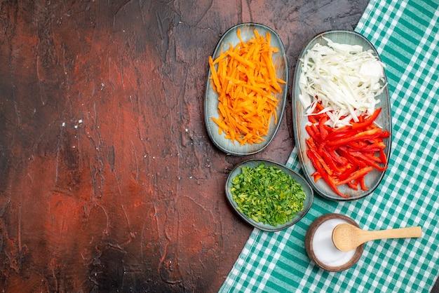 Widok z góry pokrojone warzywa kapusta marchewka i papryka z zieleniną na ciemnym stole
