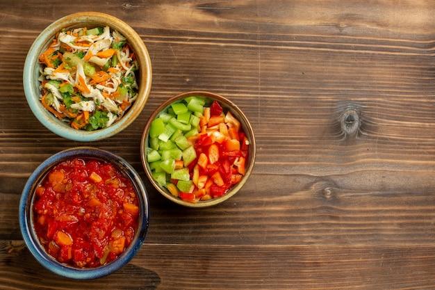 Widok z góry pokrojone warzywa papryka z pomidorami na brązowym drewnianym tle mączka warzywna jedzenie sałatka zdrowie