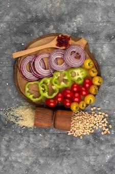 Widok z góry pokrojone warzywa, takie jak cebula i zielona papryka, wraz z całymi czerwonymi pomidorami i żółtymi pomidorami na szarej podłodze