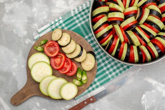 Widok z góry pokrojone warzywa, takie jak pomidory i bakłażany, świeże i gotowane na lekkim biurku danie z dojrzałych świeżych warzyw