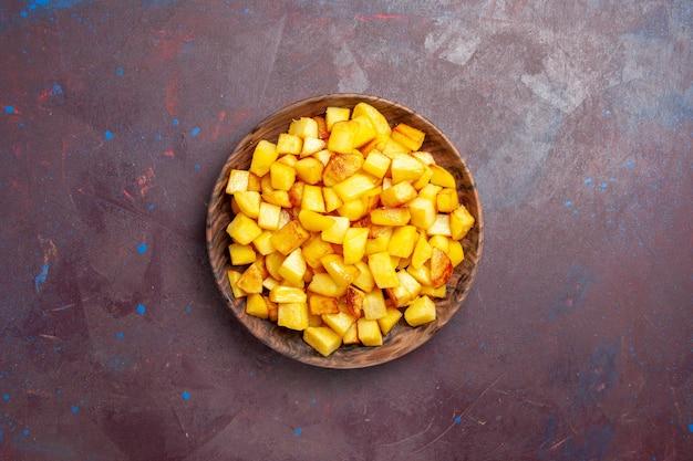 Widok z góry pokrojone ziemniaki wewnątrz brązowego talerza w ciemności