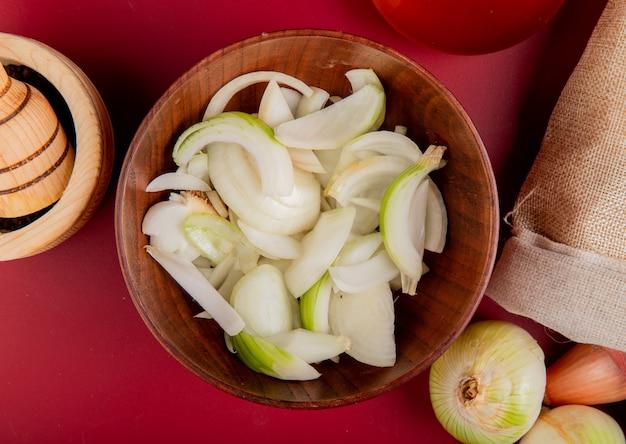 Widok z góry pokrojonej białej cebuli w misce, z której całe wysypują się z worka i czarnego pieprzu w kruszarce czosnku na czerwonej powierzchni