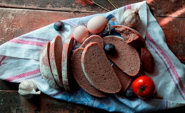 Widok z góry pokrojony czarny chleb, jajka, śliwki, rękawiczki czosnkowe i pomidory na białym obrusie.