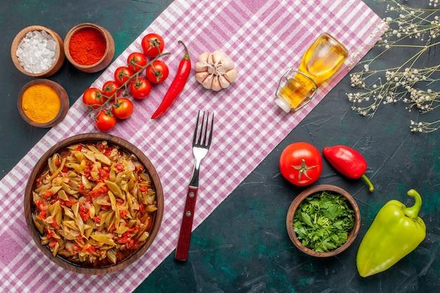 Widok z góry pokrojony posiłek warzywny z różnymi przyprawami na ciemnoniebieskim tle