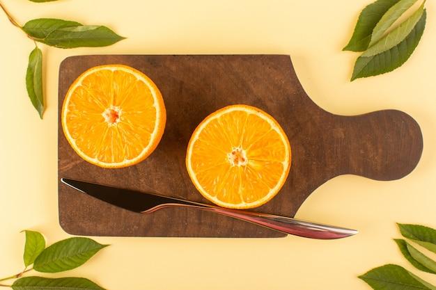 Widok z góry pokrojony w plasterki cały pomarańczowy świeży soczysty mellow wraz ze srebrnym nożem i zielonymi liśćmi na brązowym drewnianym biurku i kremowym tle cytrusowo-pomarańczowym