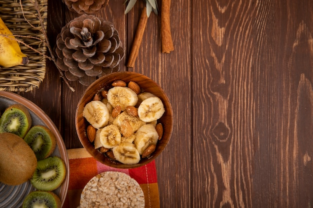Widok z góry pokrojonych bananów z migdałami w drewnianej misce, plastry owoców kiwi na talerzu i krakersy ryżowe w stylu rustykalnym z miejsca kopiowania
