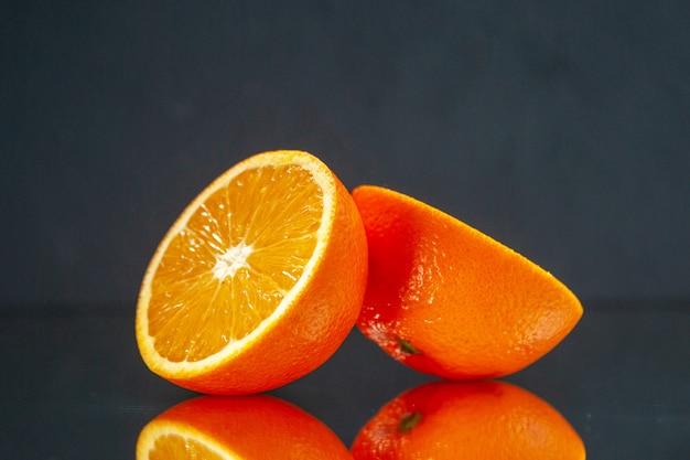 Widok z góry pokrojonych świeżych pomarańczy stojących obok siebie na świetle na czarnym tle z wolną przestrzenią