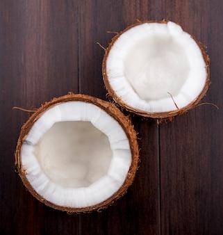 Widok z góry pół brązowych i świeżych kokosów na drewnianej powierzchni