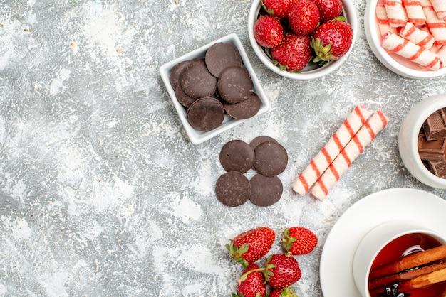 Widok z góry pół miski z truskawkami, czekoladkami, cukierkami i herbatą z anyżu cynamonowego na szaro-białym podłożu