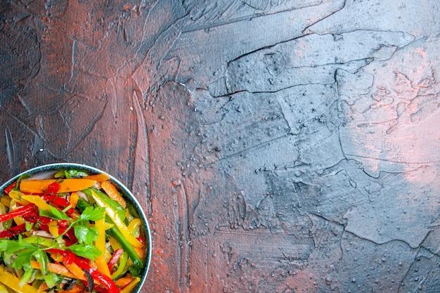 Widok z góry pół sałatki warzywnej w misce na ciemnoczerwonym stole z miejsca na kopię