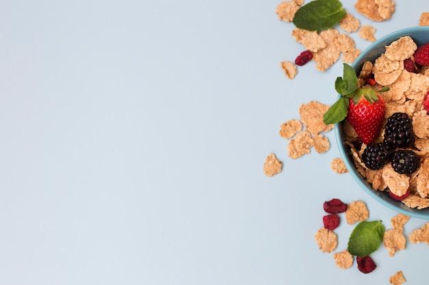 Widok z góry połowa miski z owocami i płatkami zbożowymi
