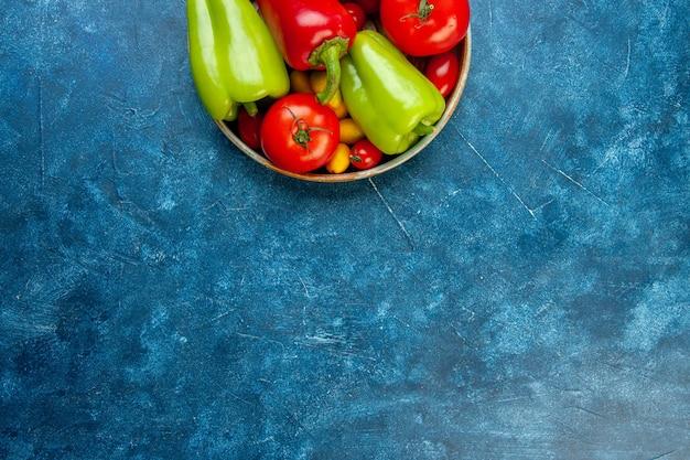 Widok z góry połowa warzyw pomidory koktajlowe różne kolory papryka pomidory w misce na niebieskim stole z miejscem kopiowania