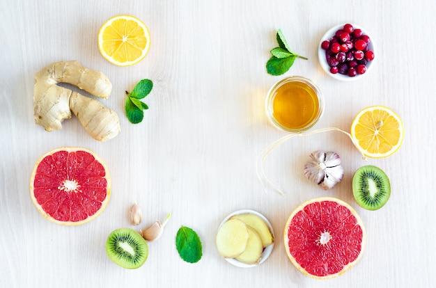 Widok z góry połówki owoców cytrusowych i produktów z witaminą c na jasnym tle drewnianych