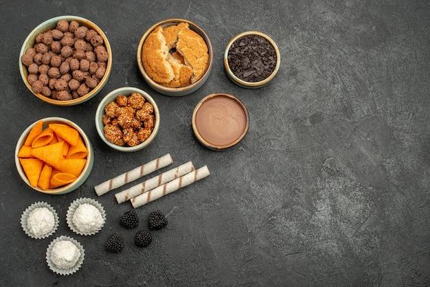 Widok z góry pomarańczowe cipsy ze słodkimi orzechami i płatkami czekolady na ciemnoszarej powierzchni posiłek przekąska śniadanie orzech