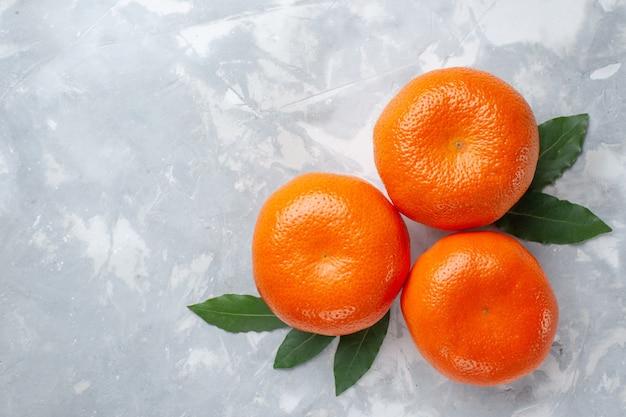Widok z góry pomarańczowe mandarynki całe cytrusy na lekkim biurku cytrusowy sok egzotyczny owoce tropikalne