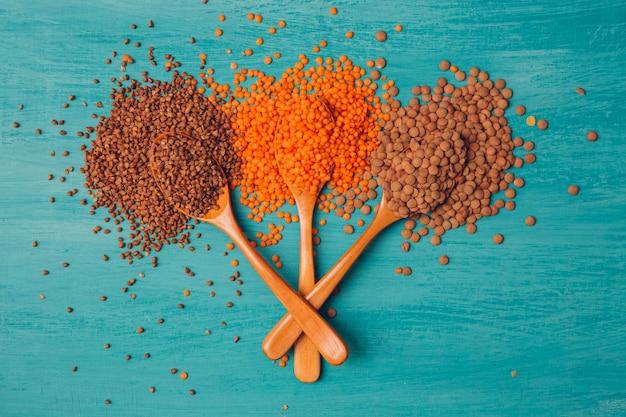 Widok z góry pomarańczowej soczewicy i kaszy gryczanej w 3 drewnianych łyżkach