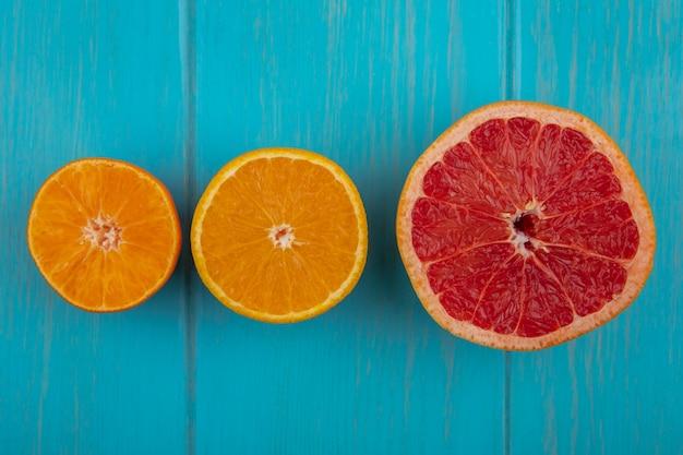 Widok z góry pomarańczowy plasterek z plasterkiem grejpfruta na turkusowym tle