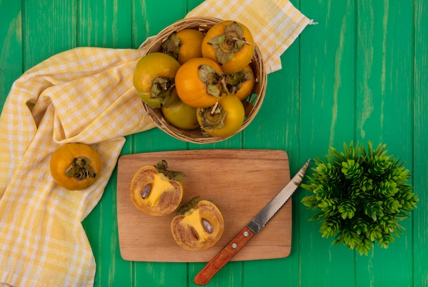 Widok z góry pomarańczowych okrągłych owoców persimmon na wiadrze z przekrojonymi na pół owocami persimmon na drewnianej desce kuchennej z nożem na zielonym drewnianym stole