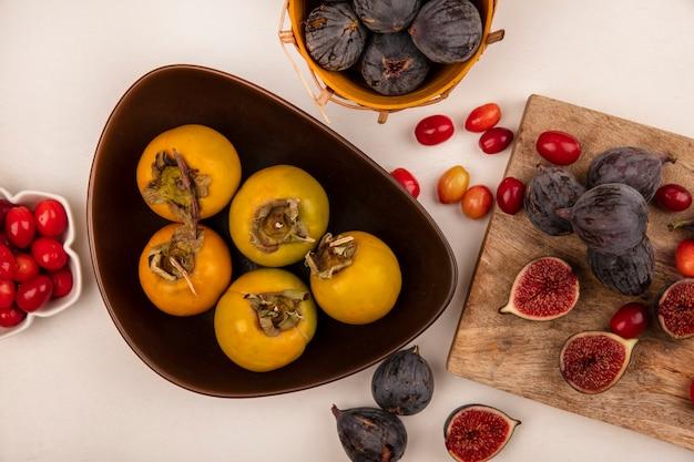 Widok z góry pomarańczowych owoców persimmon na misce z czarnymi figami na drewnianej desce kuchennej z wiśniami dereń na białym tle