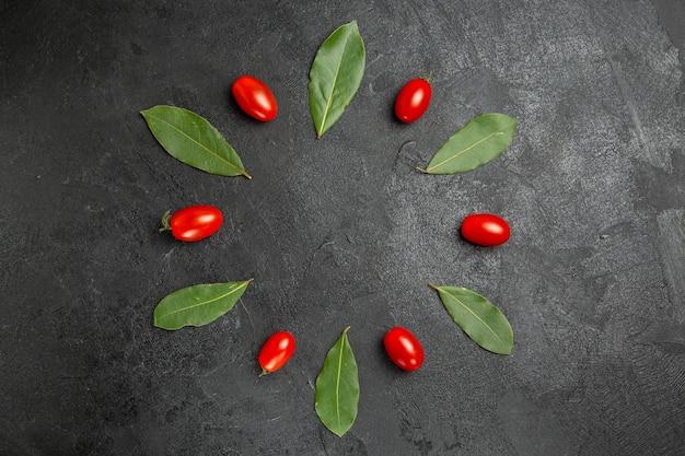 Widok z góry pomidorki koktajlowe i liście laurowe na ciemnym podłożu