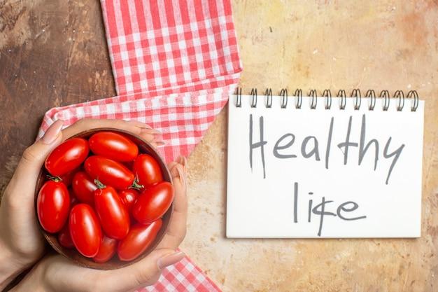 Widok z góry pomidorki koktajlowe w drewnianej misce w kobiecych rękach ręcznik kuchenny zdrowe życie napisane w notatniku na bursztynowym tle