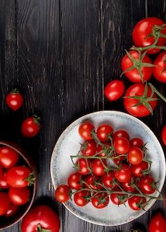 Widok z góry pomidorów w talerzu i innych na powierzchni drewnianych