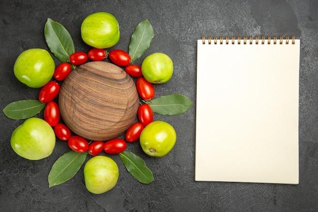 Widok z góry pomidory czereśniowe zielone pomidory i liście laurowe wokół drewnianego talerza i notatnika na ciemnym podłożu