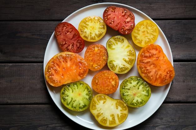 Widok z góry pomidory, pokrojone w plasterki lub na pół, różne odmiany.