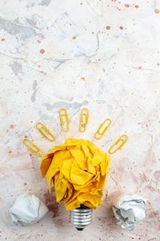 Widok z góry pomysł żarówki koncepcja z pogniecionymi żółtymi spinaczami do klejnotów na stole z wolną przestrzenią