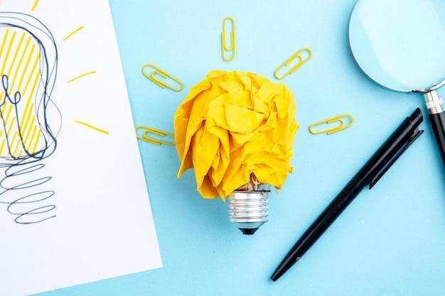 Widok z góry pomysł żarówki koncepcja z zmiętym papierem i klejnotami klipsy długopis lupa na stole