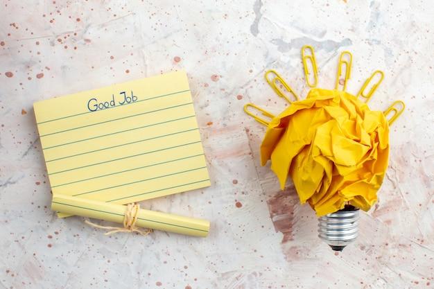 Widok z góry pomysł żarówki koncepcja z zmiętym żółtym papierem spinacze do klejnotów papier firmowy na stole