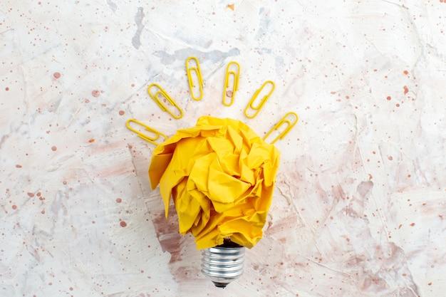 Widok z góry pomysł żarówki koncepcja z zmiętymi żółtymi spinaczami do klejnotów papieru na przestrzeni kopii stołu