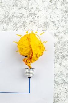 Widok z góry pomysł żarówki koncepcja z żółtym zmiętym papierem na papierze na stole